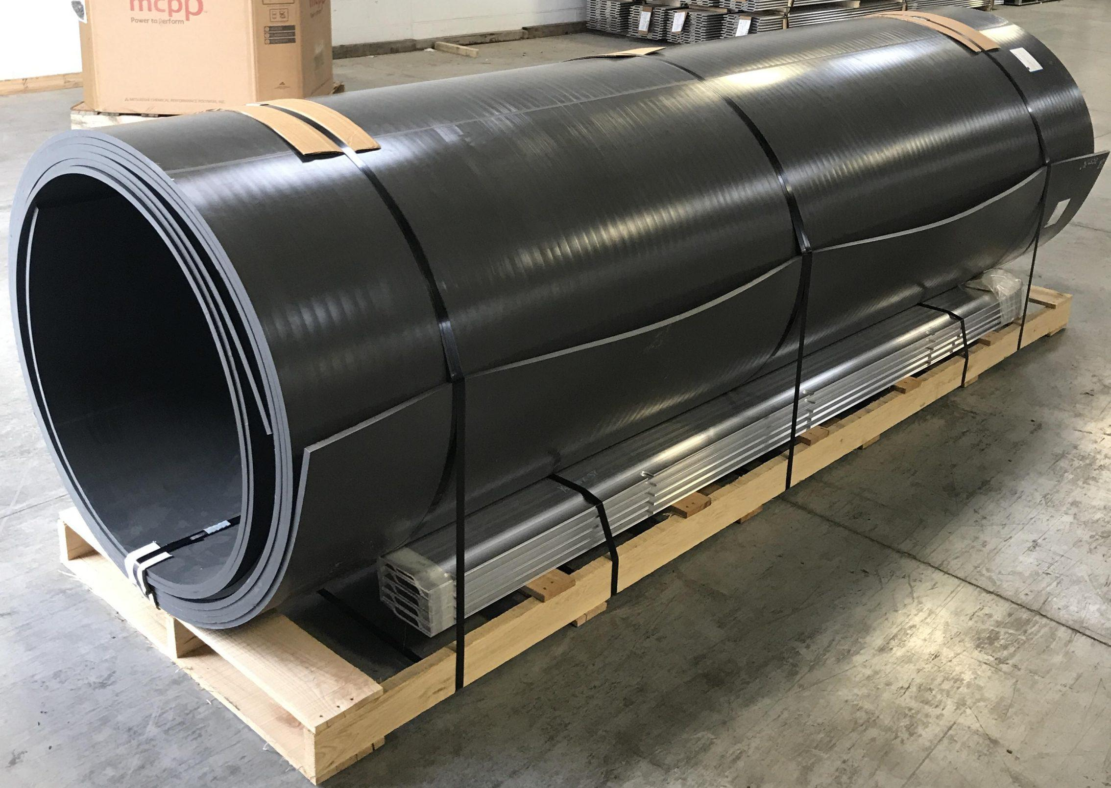photo of a roll of black truck liner material on a pallet
