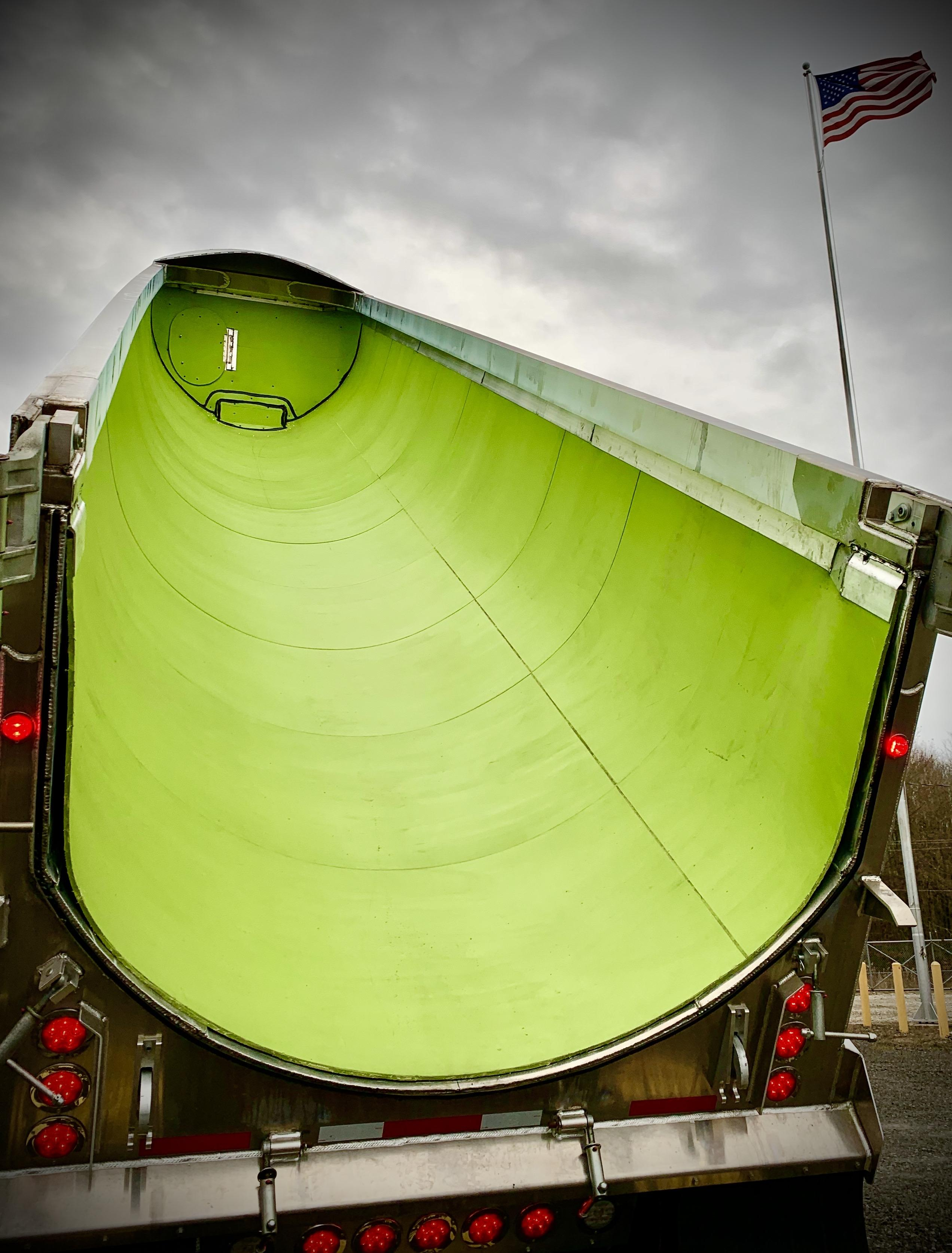 photo of a dump truck with curved green liner